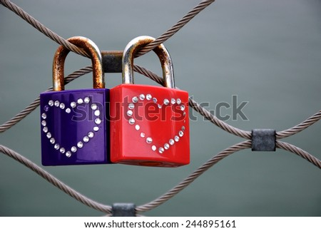 Two grungy love padlocks with heart decoration attached to the bridge in Paris. Valentine's day background.  - stock photo