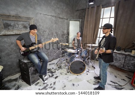 Two guitarists and drummer play in room powdered with snow - stock photo