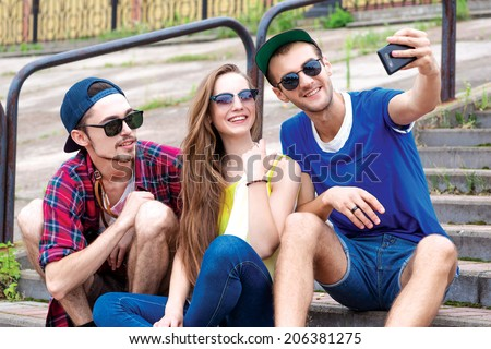 Two guys and a girl in sunglasses photographed on a mobile phone. Young friends have fun together on the street and smile at each other. Funny guys make Selfie - stock photo