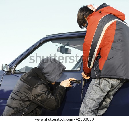 Two guys breaking door of a car - stock photo
