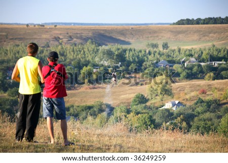Two guys compete on radio controlled helicopter , good landscape - stock photo