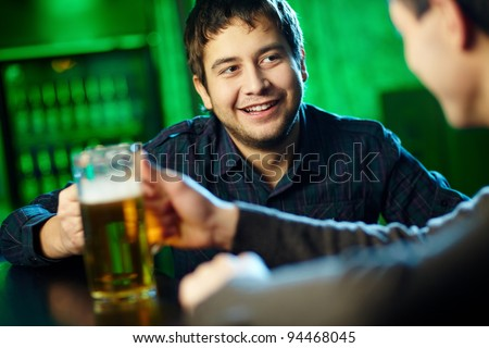 Two guys hanging out in bar with mugs of beer - stock photo