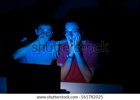 Two guys in front of a computer screen completely shocked at what they see - stock photo