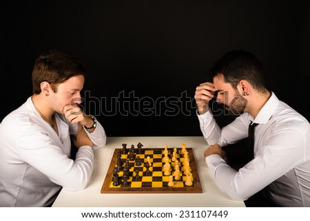 Two guys in their 20s concentrated playing chess - stock photo