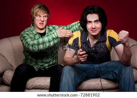 two guys playing video games on red background