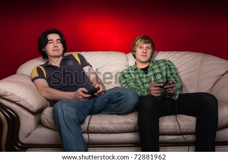 two guys playing video games on red background - stock photo