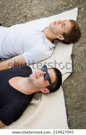 Two guys relaxing together lying in their jeans on a blanket alongside a lake - stock photo
