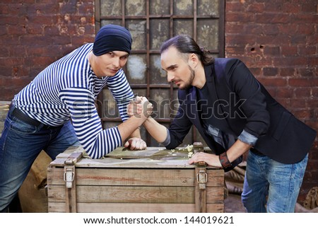 Two guys wrestle on wooden chest in depot - stock photo