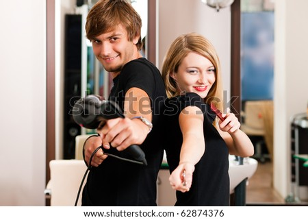 Two hairdresser - man and woman - posing for the camera in the hairdresser's shop - stock photo