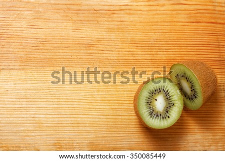 Two half fresh kiwi fruit on wooden cutting board. Top view, copyspace. - stock photo