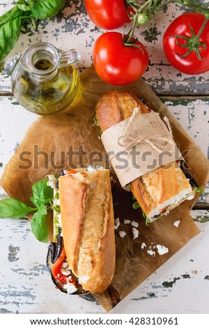 Two half of vegetarian baguette submarine sandwich with grilled eggplant, pepper and feta cheese served on baking paper with tomatoes and olive oil over old white wooden background. Top view