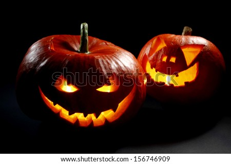 Two halloween pumpkins on black background - stock photo