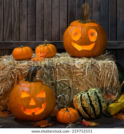 Two halloween pumpkins with a bale of hay and other gourds - stock photo