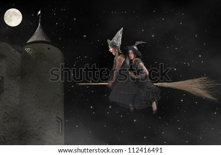 two halloween witches flying on a broom - stock photo