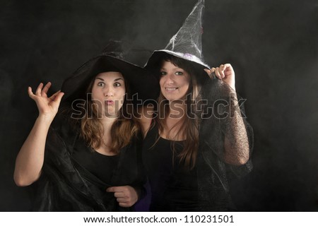 two halloween witches on dark background - stock photo