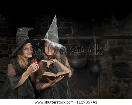 two halloween witches with apple and book - stock photo