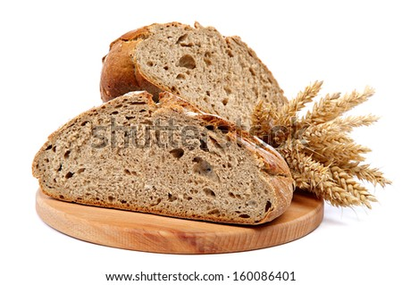 Two halves a loaf of rye bread and wheat ears isolated on white background. - stock photo