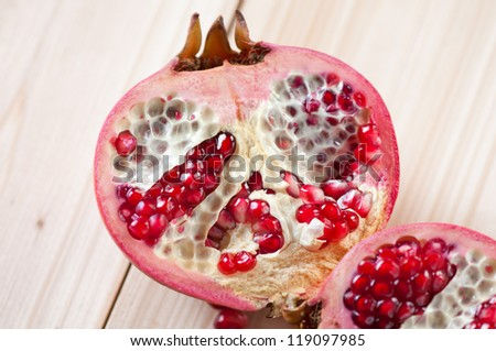 Two halves of a pomegranate on wooden boards, studio shot - stock photo