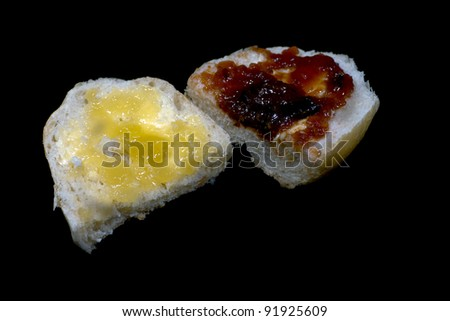 Two halves of buns with honey and jam on the black background. - stock photo