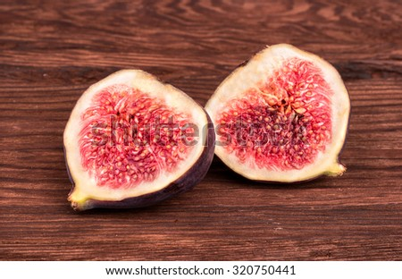 Two halves of sliced fresh figs on a wooden background