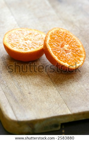 Two halves of sliced juicy oranges on wooden board - stock photo