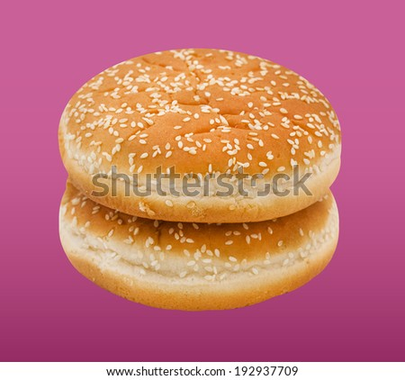 Two hamburger bun with sesame seeds on pink background.