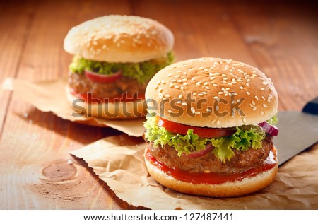 Two hamburgers and french fries with sesame bun on brown paper - stock photo