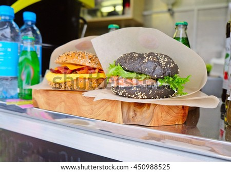 two hamburgers at the counter of a street cafe