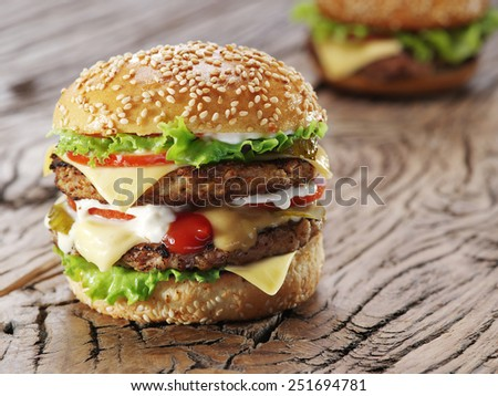 Two hamburgers on old wooden table. - stock photo