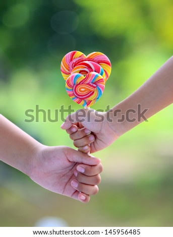 Two hand hold lollipop on green background - stock photo