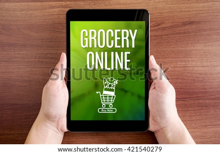 Two hand holding tablet with Grocery Online and icon on screen at dark brown table top,Digital business concept. - stock photo