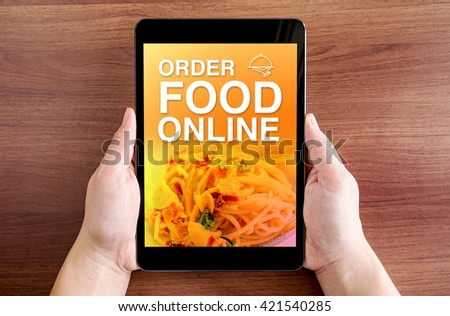 Two hand holding tablet with Order food online and icon on screen at dark brown table top,Digital business concept. - stock photo