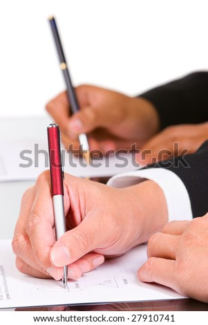 Two hand is signing the document, focused mainly on the front hand.