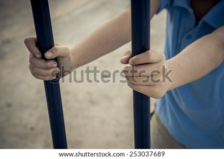 Two hand of a boy holding the black iron bar