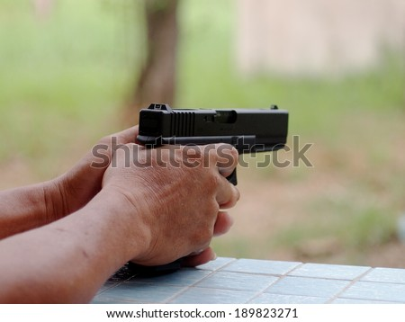 two hand of an unidentified senior male holding and shooting black air soft gun model of a replica real pistol in green area in a garden of a country house with fun and serious mood - stock photo