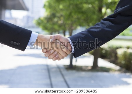 Two hands are gripping each other in a handshake. - stock photo