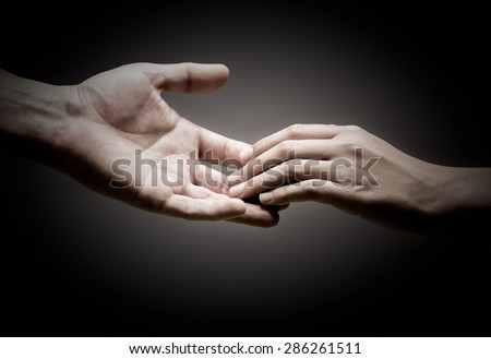 two hands are touching each other over black background, concept of solidarity or empathy. - stock photo
