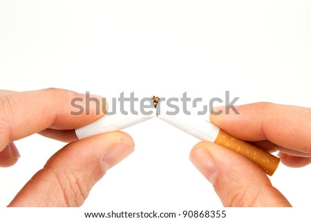 Two hands breaking a cigarette in half in front of a white background - stock photo