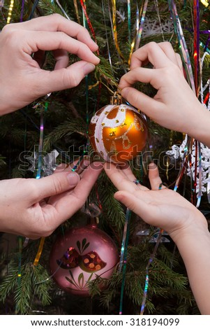 two hands, child and women, decorating Christmas tree
