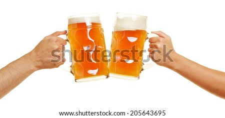 Two hands clinking beer glasses for a cheer - stock photo