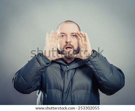Two hands covering her mouth on the sides show a loud cry. young guy . Photo. Men loudly calling someone. - stock photo