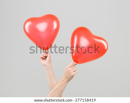 two hands crossed holding heart shape balloons against grey background - stock photo