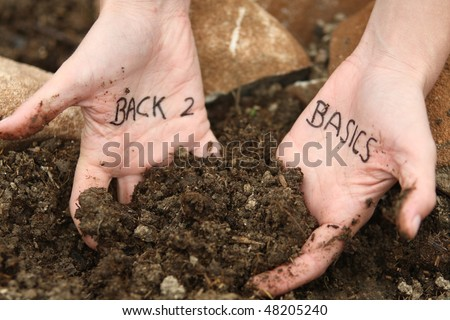 Two hands digging in earth, with a message written on the palms