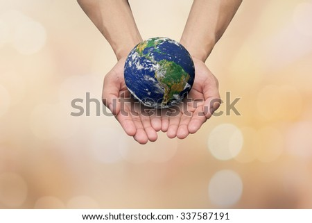 Two hands gesture holding the earth on blurred map over blue sky backgrounds. Elements of this image furnished by NASA - stock photo