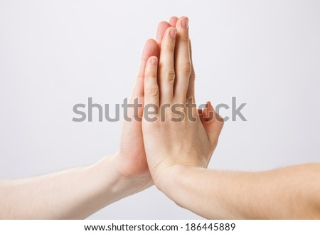 Two hands giving high five to each other - stock photo