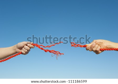 Two hands gripped around broken orange rope leaving a gap, isolated with blue sky as background and copy space.