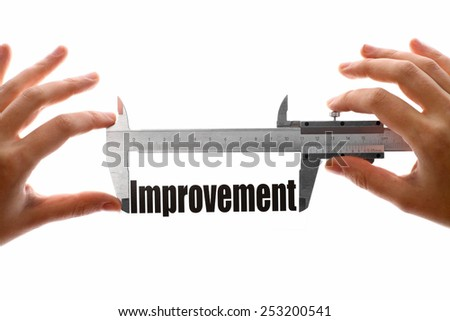 "Two hands holding a caliper, measuring the word ""Improvement"". - stock photo"