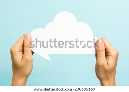 Two hands holding a cloud on blue background. Internet concept. - stock photo