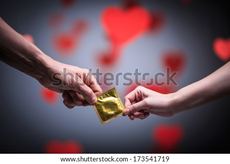 Two hands holding a condom - stock photo
