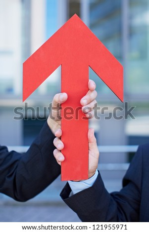 Two hands holding a red arrow pointing up - stock photo